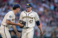 Michigan Wolverines pitcher Tommy Henry (47) is greeted in between innings by teammate Jack Bredeson (34) against the Vanderbilt Commodores during Game 1 of the NCAA College World Series Finals on June 24, 2019 at TD Ameritrade Park in Omaha, Nebraska. Michigan defeated Vanderbilt 7-4. (Andrew Woolley/Four Seam Images)