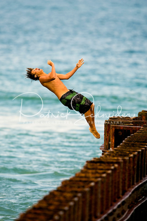 A beach goer jumps into the ocean from a sea wall along Cape Hatteras Beach, near the Cape Hatteras Lighthouse. The Cape Hatteras Light house is one of the most recognized American lighthouses and a famous symbol of North Carolina. Cape Hatteras is one of the few North Carolina lighthouses where visitors can climb the inside stairs to the top. Cape Hatteras has white and black spiral bands and a red brick base. The lighthouse's beacon of light can be seen some 20-miles out to sea and has warned sailors for more than 100 years about the treacherous Diamond Shoals, the shallow sandbars which extend some 14 miles out into the ocean off Cape Hatteras. Charlotte NC photographer Patrick Schneider has extensive photo collections of the following lighthouses: Bodie Island Lighthouse, Bald Head Island Lighthouse, Cape Fear Lighthouse, Cape Hatteras Lighthouse, Cape Lookout Lighthouse, Currituck Beach Lighthouse, Diamond Shoal Lighthouse, Federal Point Lighthouse, Oak Island Lighthouse, and Ocracoke Lighthouse on Ocracoke Island.