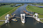 Foto: VidiPhoto<br /> <br /> DRIEL – Aan de stuw bij Driel zijn in opdracht van Rijkswaterstaat de voorbereidende werkzaamheden begonnen voor het laatste deel van een unieke megaklus. De komende maanden wordt de zuidelijke vizierschuif vervangen. De stalen ronde boog voor de stuw wordt in drie stukken gezaagd en vervolgens vervangen door drie nieuwe delen. De werkzaamheden duren zo'n 16 weken als het waterpeil in de Rijn niet stijgt. Twee jaar geleden werd de noordelijk boog vernieuwd. Dat werk was eerder ingepland, maar moest uitgesteld worden omdat bij voorbereidingswerkzaamheden een duiker om het leven kwam. De waterkeringen van Amerongen, Hagestein en Driel in de Rijn, hebben de enige stuwbogen ter wereld. De vizierschuiven van Amerongen en Hagestein zijn inmiddels vervangen. Dit deel bij Driel is de laatste klus van het megaproject met een aanneemsom van 100 miljoen euro. Hoofdaannemer is Siemens. De stuwen in de Rijn zijn nodig om bij droogte het schaarse zoetwater goed te kunnen verdelen voor met name de landbouw.