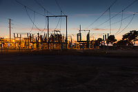 An electric power substation, crisscrossed with power lines and glowing with sunset's last light and its own lamps.