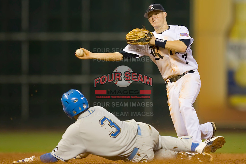 Brock Holt #7 of the Rice Owls turns a double play as Steve Rodriguez #3 of the UCLA Bruins slides into second base in the 2009 Houston College Classic at Minute Maid Park February 27, 2009 in Houston, TX.  The Owls defeated the Bruins 5-4 in 10 innings. (Photo by Brian Westerholt / Four Seam Images)