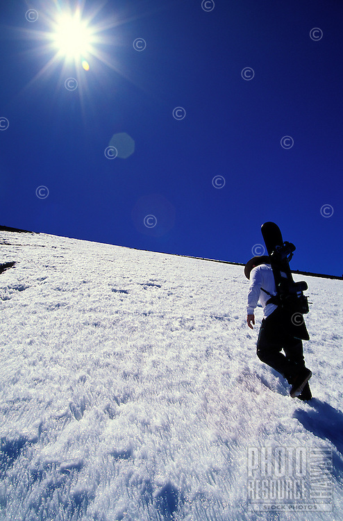 Snowboarder heads up the slope of Mauna Kea on the Big Island of Hawaii with a blazing white sun set against a vivid blue sky.