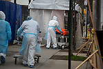 Healthcare workers wheel the bodies of COVID-19 victims to a refrigerated trailer used as a temporary morgue outside of Wyckoff Heights Medical Center in the Brooklyn borough of New York City on April 5, 2020.  Photograph by Michael Nagle
