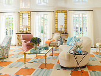In the living room, things begin with bright and white: The walls are plaster and the ceiling is a white lacquer. A nearly wall-to-wall blue and orange area rug, inspired by a Swedish design, nods to sunsets and works to pull together the colour-splashed room. A curved sofa floats in the centre to create movement in the lively space.