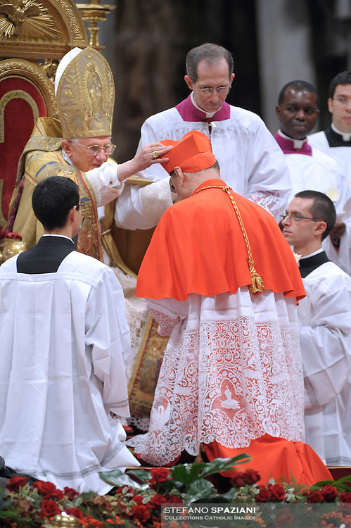 Italian newly appointed Cardinal Gianfranco Ravasi (C) gets his biretta, the square red hat symbolising the blood of the martyrs, from Pope Benedict XVI (L) on November 20, 2010 during a consistory at St Peter's basilica at The Vatican. 24 Roman Catholic prelates join today the Vatican's College of Cardinals, the elite body that advises the pontiff and elects his successor upon his death