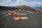 Wooden boards (sleds) and orange bags of protective suits sit on top of active volcano Cerro Negro, Nicaragua