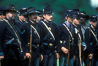 Reenactment of Union Civil War infantry standing in formation holding weapons.