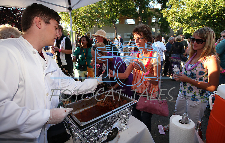 Dillon Hekhuis serves meatballs to Ruth and Laura Redmon at the Tahoe Ridge Winery booth during the 20th annual Taste of Downtown event in Carson City, Nev., on Saturday, June 15, 2013. The event features 44 local restaurants in a fundraiser for the Advocates to End Domestic Violence.<br /> Photo by Cathleen Allison