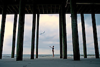 A boy flies his kite on the beaches of Dauphin Island, Alabama, a barrier island located three miles south of the mouth of Mobile Bay in the Gulf of Mexico. This island, which is approximately 14 miles long and less than two miles wide, appears to have fully recovered from the impact of Hurricane Katrina (2005) and the BP Deepwater Horizon Oil Spill in 2010. Both events greatly reduced tourism income (fewer people came to the island) and local business owners say many establishments went out of business. Today they say they're looking forward to a rebounding tourism business.