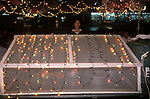 Zhejiang Province People Republic of China. Coloured lights illuminate and draw attention to an out door food stand  Hangzhou 1990S