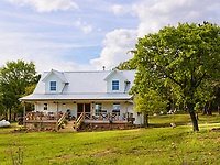The exterior of a self-built country house with covered veranda.