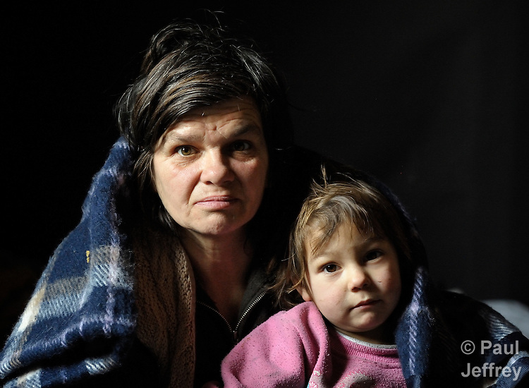 Arbanac Sofija and her 3-year old daughter Caka huddle under a blanket - provided by Church World Service - inside their meager home in an illegal Roma settlement in Belgrade, Serbia, in February 2012. The poor family has been told it will be evicted by city officials in March 2012 to make way for new high-rise office buildings.  In April 2012, the Serbian Orthodox family was forcibly evicted from the city center and given a metal shipping container in Makis, at the edge of Belgrade, where they could live. After several weeks, they were evicted from the shipping container because of her husband's repeated fights with his neighbors, and at the end of 2012 lived in an informal Roma squatter settlement in nearby Palilula. In 2009, they had been evicted from another settlement in Belgrade..