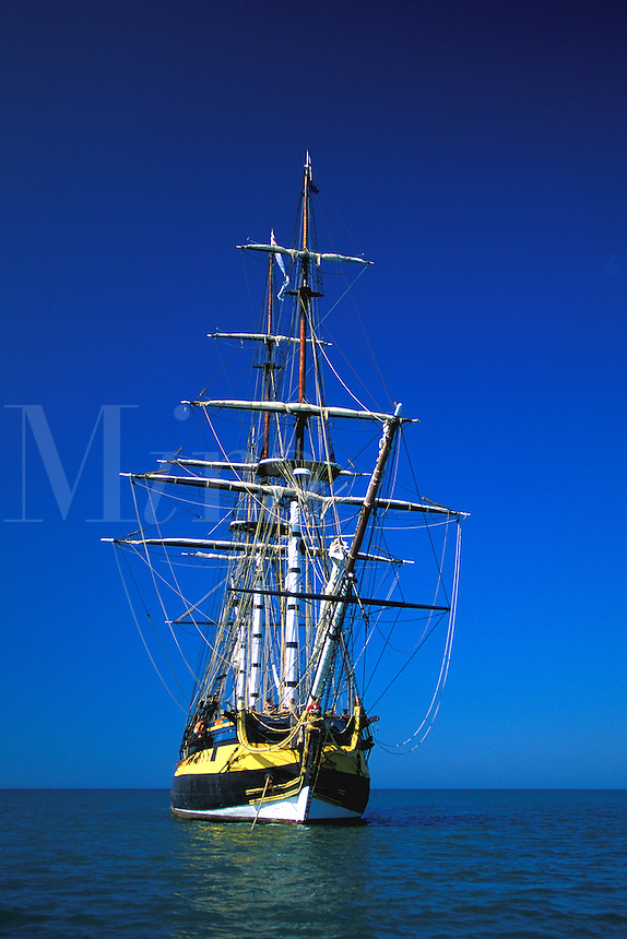 Square rigged sailing vessel at anchor.