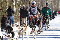 Cindy Abbott and team run past spectators on the bike/ski trail during the Anchorage ceremonial start during the 2014 Iditarod race.<br /> Photo by Britt Coon/IditarodPhotos.com