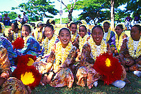 People in costumes with leis and feather rattles uli uli at the annual aloha week parade