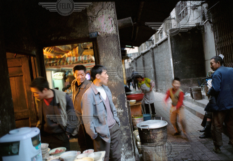 Migrant workers wait to eat at a cheap restaurant.