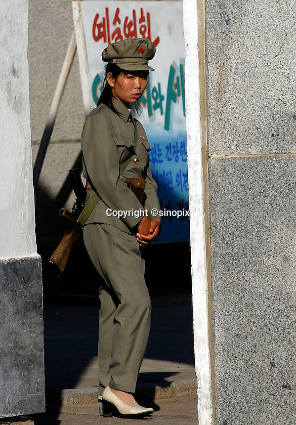 """Female North Korean soldier in Pyongyang, North Korea. The DPRK (Democratic People's Republic of Korea) is the last great dictatorship where the people are bombarded with images of the """"Eternal President"""" Kim Il-sung who died in 1994 and his son and current leader Kim Jong-il who are worshipped like a God."""