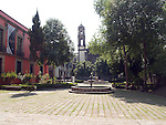 TREE LINED PLAZA WITH FOUNTAINS AND CHURCH STEEPLE IN BACKGROUND