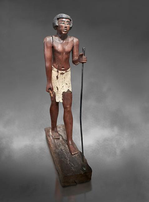 Ancient Egyptian wooden statue of Shemes,  Middle Kingdom (1980-1700 BC), tomb of Shimes, Asyut. Egyptian Museum, Turin.  Grey background.<br /> <br /> In 1908 in Asyut, Egypt an intact tomb was discovered of an official named Shemes, it contained many rich grave goods. Two rectangular Coffins, one for Shemes and the other for a woman called Rehuerausen, possibly his wife. They carry typical Middle Kingdom decorations,