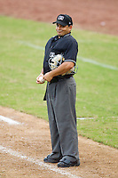Home plate umpire Jose Esteras makes a face at the Hickory Crawdads dugout while they complain about strike calls during a South Atlantic League game against the Kannapolis Intimidators at  L.P. Frans Stadium August 1, 2010, in Hickory, North Carolina.  Photo by Brian Westerholt / Four Seam Images