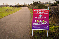 A bilingual sign along a walking trail advises visitors:  Prevent the Spread of Covid- 19 - Wear a Mask - Social Distance 6'.  At the  Martin Luther King Jr. Regional Shoreline in Oakland, California,