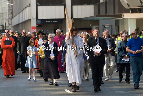 "Easter Good Friday. London UK. Walk of Witness.  ""The Crucifixion on Victoria Street."" A Christian Cross is carried from the Methodist Central Hall to Westminster Cathedral to Westminster Abbey."
