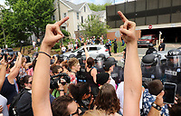 Hand gestures are used by protestors as Ku Klux Klan members to leave in their cars after rallying in Jackson Park Saturday in Charlottesville, Va.  Photo/Andrew Shurtleff
