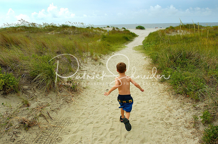A young boy races down a sandy path to the ocean beach on Sullivan's Island, SC.