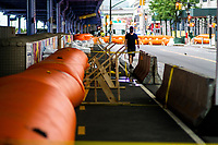 """NEW YORK, NY - AUGUST 4: A man walks next to water barriers used to prevent flooding at the South Street Seaport as city gets ready for tropical storm Isaias on August 4, 2020 in New York City. The Tri-State area """"New York, New Jersey and Connecticut"""" is preparing for torrential rain, strong winds from Tropical storm Isaias. (Photo by Eduardo MunozAlvarez/VIEWpress)"""
