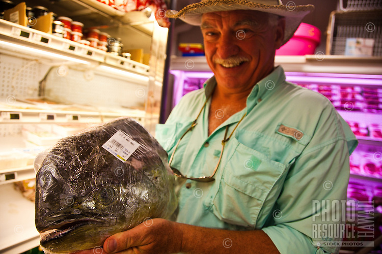 Tourist displays mahi mahi head for display in supermarket aisle