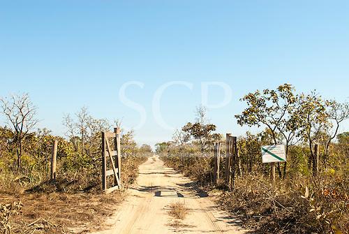 """Mato Grosso State, Brazil. Entrance to the Indigenous Park of the Xingu with FUNAI sign""""Protected Land, no access for strangers""""."""