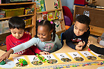 Education Preschool 4 year olds group of children playing math concepts game, rolling die and jumping toy frogs along number line