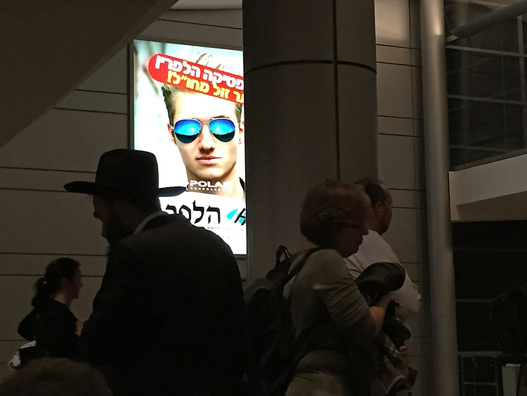 """24. """"Polarities at Ben Gurion Airport"""": a Hasid ultra-orthodox Jew paired with secularized travelers who walk by an advert for polarized sunglasses, near Tel Aviv.<br /> <br /> As I prepare to return home after honoring my parents by planting a tree, I see this apocryphal scene at the airport. A Hasid is walking one way wearing traditional religious garb, while travelers dressed in more modern, secular clothing walk in the opposite direction. In the background, a spotlit ad features a fashionable young man wearing polarized sunglasses. <br /> <br /> Surely, this image highlights Israel's polarities! Looking at it, I wonder what values will ultimately triumph in this complex land.  Will superficial, destructive desires outweigh kindness and understanding? Will we ever make peace and find common ground?<br /> <br /> And will I go back to Israel to see what transpires?  I haven't decided. But I hope Israel will be there, despite its thorns and brambles, should I choose to return."""