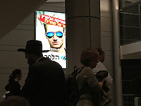 "24. ""Polarities at Ben Gurion Airport"": a Hasid ultra-orthodox Jew paired with secularized travelers who walk by an advert for polarized sunglasses, near Tel Aviv.<br />
