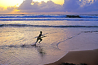 Young boy running with boogie board in hand at Rockey Point, North Shore