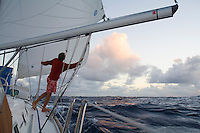 Man at the rail of a sailboat under way at sunset in the trade winds, during a Pacific crossing