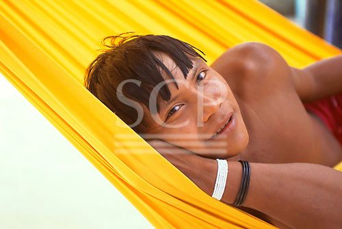 Brazil. Yanomami Indian man enjoying a rest in a hammock.