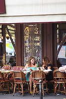 Le Bistrot du Peintre cafe bar terrase outside seating on the sidewalk. Two young women having a drink and chatting on a wicker sofa The Bistrot du Peintre is an old fashioned Paris café cafe bar restaurant of art nouveau design with polished brass, mirrors and old signs