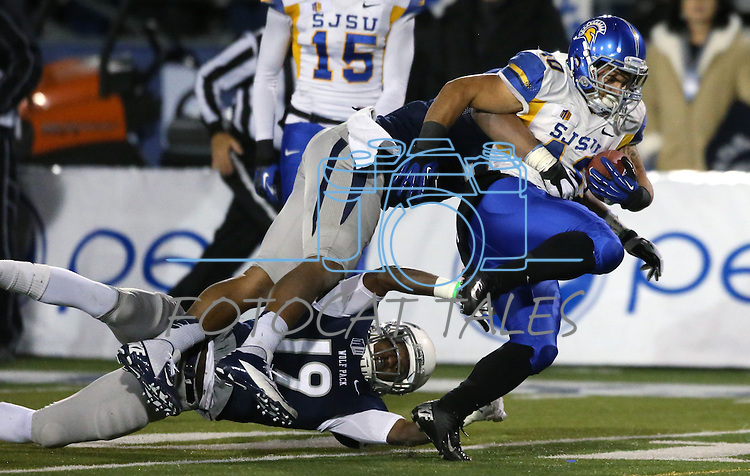 Nevada's Evan Favors, lower left, and Jonathan McNeal tackle San Jose State's Jarrod Lawson in an NCAA college football game in Reno, Nev., on Saturday, Nov. 16, 2013. (AP Photo/Cathleen Allison)