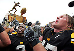 Iowa defensive lineman Mitch King, right, and defensive back Harold Dalton lead the Hawkeyes in the Iowa fight song while teammates jubilantly hoist the Cy-Hawk Trophy after defeating Iowa State 17-5 at Kinnick Stadium in Iowa City, Saturday September 13, 2008.