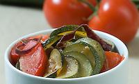Zucchini squash  and tomato skillet meal in white bowl studio