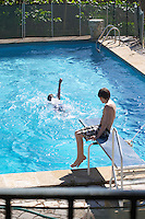 A blue swimming pool with two teenage boys playing Clos des Iles Chambres d'Hotes Bed and Breakfast Le Brusc Six Fours Cote d'Azur Var France