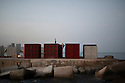 Spain - Barcelona - Young men training on top of containers located along the seaside.