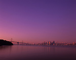 Retro Image of San Francisco downtown skyline at sunrise with city buildings reflected in serene, calm bay from Treasure Island, San Francisco, California USA