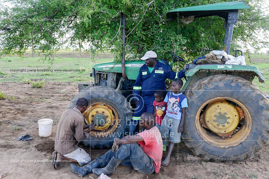 ZAMBIA, Mazabuka, Chikankata area, medium scale farmer Stephen Chinyama with John Deere Tractor, patching a flat tube of a tire at the field