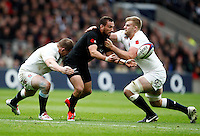 Photo: Richard Lane/Richard Lane Photography. England v New Zealand. QBE Autumn International. 08/11/2014. New Zealand's Aaron Cruden offloads as he is tackled by England's Dylan Hartley and Chris Robshaw.