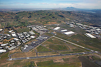 aerial photograph of Napa County Airport (APC), Napa, California, large warehouses have been built around the airport, a portion of American Canyon is visible in the background right, Mt. Diablo in the background