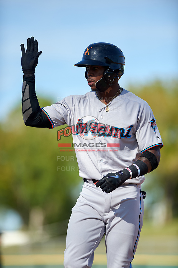 Salt River Rafters center fielder Monte Harrison (4), of the Miami Marlins organization, high fives his first base coach after hitting an RBI-single during the Arizona Fall League Championship Game against the Peoria Javelinas at Scottsdale Stadium on November 17, 2018 in Scottsdale, Arizona. (Zachary Lucy/Four Seam Images)
