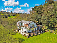 BNPS.co.uk (01202) 558833.<br /> Pic: LillicrapChilcott/BNPS<br /> <br /> A stylish modern home in a wooded valley and minutes from a beautiful sandy beach is on the market for £1.5m.<br /> <br /> Maenvale sits in a secluded valley surrounded by picturesque woodland and with views over Maenporth Beach and across to Falmouth Bay.<br /> <br /> The previous bungalow on the site was severely leaning and had inadequate foundations so Tristram Stott Architects built this modern replacement in 2007.<br /> <br /> The house has over 2,100 sq ft with a full-height galleried reception hall, triple aspect sitting room, one bedroom with an en suite, two further double bedrooms and a family bathroom on the ground floor.