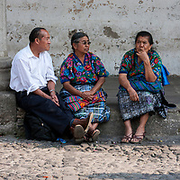 Antigua, Guatemala.  Man and Two Women Sitting, Talking, Plaza de Armas.  Semana Santa.